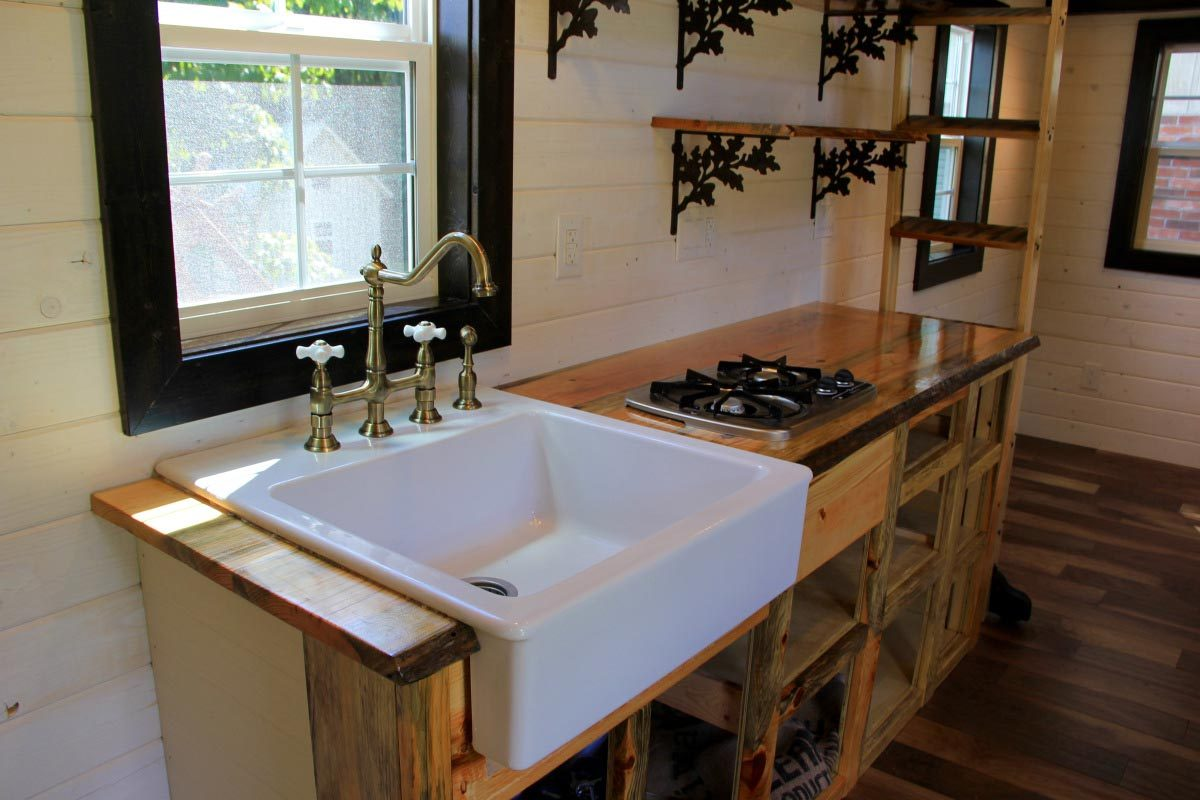 Kitchen area features open faced cabinets - Fort Austin by Brevard Tiny House
