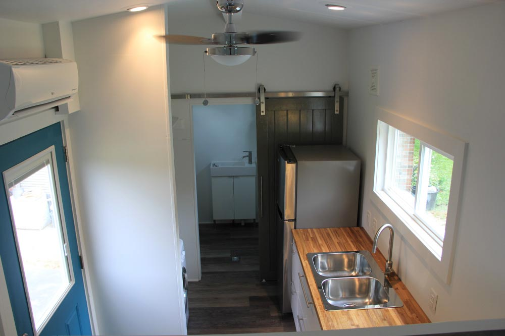 Kitchen with full refrigerator and double sink - Every Tiny Moment by Brevard Tiny House