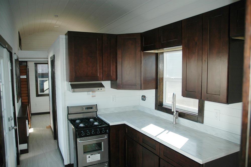 Kitchen with mahogany cabinets and Corian countertop - Carpathian by Tiny Idahomes