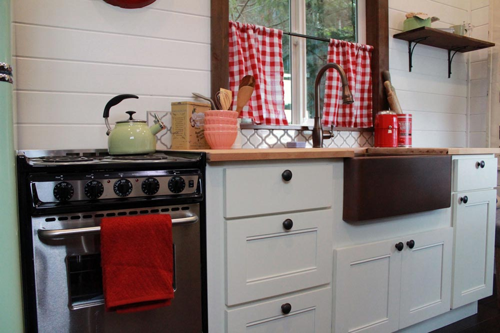 Kitchen with white cabinets and farm sink - Family of Four by Tiny Heirloom