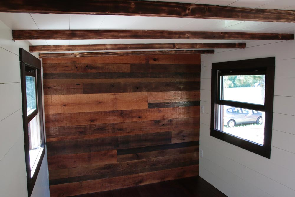 Reclaimed pallet accent wall in bedroom - Wind River Tiny Homes